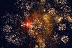 Fuegos artificiales brillantes de oro de estallido contra un cielo nocturno Imagen de archivo libre de regalías