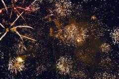Fuegos artificiales brillantes de oro de estallido contra un cielo nocturno Fotos de archivo