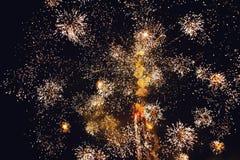 Fuegos artificiales brillantes de oro de estallido contra un cielo nocturno Imágenes de archivo libres de regalías
