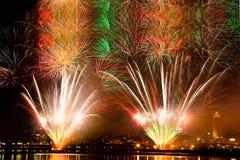 Fuegos artificiales coloridos con la ciudad en el cielo negro Imagenes de archivo