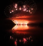 Fuegos artificiales coloridos con la reflexión en el lago Imagen de archivo libre de regalías