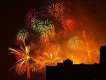 Fuegos artificiales coloridos con la silueta del edificio Imagenes de archivo