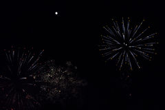Fuegos artificiales coloridos y bengalas blancas debajo de una Luna Llena brillante Fotografía de archivo