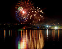 Fuegos artificiales con la reflexión en agua Imagen de archivo libre de regalías