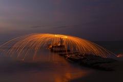 Fuegos artificiales de giro del hombre en la costa costa imagen de archivo libre de regalías