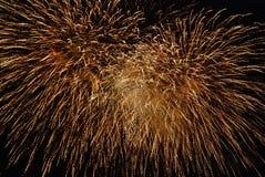 Fuegos artificiales del color de oro, contra el cielo nocturno negro Imagen de archivo libre de regalías