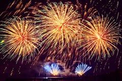 Fuegos artificiales del día de fiesta del color de oro en un fondo negro del cielo Fotografía de archivo