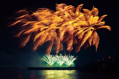 Fuegos artificiales del día de fiesta del color de oro en un fondo negro del cielo Fotos de archivo