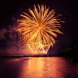 Fuegos artificiales del día de fiesta del color de oro en un fondo negro del cielo Foto de archivo libre de regalías
