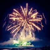 Fuegos artificiales del día de fiesta del color de oro en un fondo negro del cielo Imagenes de archivo
