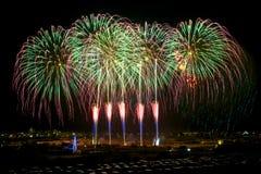 Fuegos artificiales Diversos fuegos artificiales asombrosos coloridos con la luna, el fondo oscuro del cielo y la casa se enciend Fotos de archivo