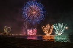 Fuegos artificiales en el agua vista de la playa, en Barcelona Fotografía de archivo libre de regalías