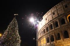 Fuegos artificiales en el colosseum con un árbol de navidad Imagen de archivo libre de regalías