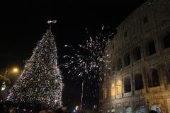 Fuegos artificiales en el colosseum con un árbol de navidad Imagenes de archivo