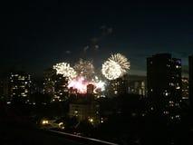 Fuegos artificiales en la noche sobre edificios fotos de archivo