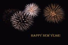 Fuegos artificiales en un fondo oscuro y un ` de la Feliz Año Nuevo del ` del texto Foto de archivo