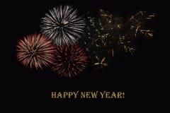 Fuegos artificiales en un fondo oscuro y un ` de la Feliz Año Nuevo del ` del texto Foto de archivo libre de regalías