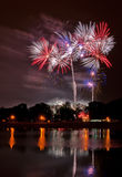 Fuegos artificiales enormes con la reflexión en el lago Fotografía de archivo
