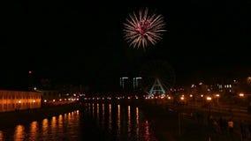 Fuegos artificiales festivos brillantes en la ciudad en el cielo nocturno sobre el río en el terraplén almacen de video