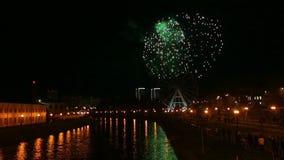 Fuegos artificiales festivos en el cielo nocturno sobre el río metrajes