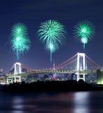 Fuegos artificiales que celebran sobre el puente del arco iris de Tokio en la noche Foto de archivo