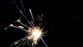 Fuegos artificiales que queman en un fondo negro, enhorabuena, saludos, partido, Feliz Año Nuevo de la bengala almacen de metraje de vídeo