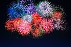 Fuegos artificiales rojos, de oro, azules asombrosos sobre el cielo nocturno Foto de archivo