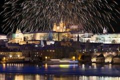 Fuegos artificiales sobre el castillo gótico nevoso colorido de Praga de la noche con Charles Bridge, República Checa Fotografía de archivo libre de regalías