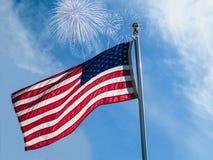 Fuegos artificiales sobre una bandera americana en el cielo nublado fotos de archivo libres de regalías