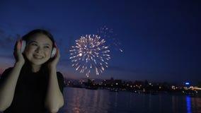 Fuegos artificiales y música que escucha de la muchacha en auriculares almacen de metraje de vídeo