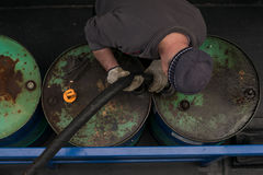 Fuel charging on boat. Man loading the barrels with fuel stock photography