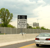 Fuel conservation, and pollution control HOV lane. Highway sign stating 2 person minimum to help conserve fuel, and reduce pollution Royalty Free Stock Photos
