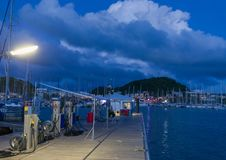 Fuel dock marina at night in Le Marin, Martinique. Sailboats in background, dark blue sky Stock Photos