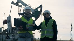 Fuel extraction site with one male expert giving instructions to another one. Energy, oil, gas, fuel pumping rig. stock footage