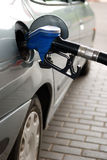 Fuel filling at gas station. Fuelling nozzle inserted into petrol tank at gas station for gasoline filling Royalty Free Stock Image