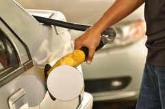 Fuel filling at gas station. Close up of the hand of a motorist, filling his car with unleaded petrol. A common environment can be seen in the petrol pump stock images