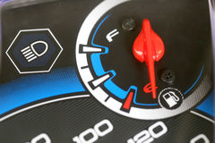 Fuel gauge with warning indicating low fuel tank. Stock Photos