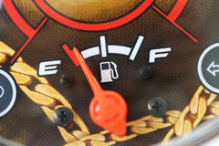 Fuel gauge with warning indicating low fuel tank. Stock Image