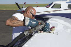 Fuel nozzle filling up aircraft Royalty Free Stock Image