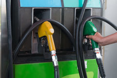 Fuel nozzle at a gas station. Fuel nozzle in hand at a gas station stock photography