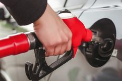 Fuel nozzle. Man hand is inserting a fuel nozzle in a gas tank. Car gas station. Refueling concept stock photo