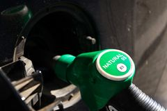 Fuel nozzle with new EU labeling circle gasoline type filling car tank from petrol station dispenser, black car. Fuel nozzle with new EU labeling circle gasoline stock photography