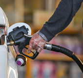 Fuel nozzle in pouring to car. Royalty Free Stock Photography
