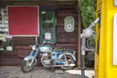 Fuel oil dispenser with old motorcycle blurry background Royalty Free Stock Image