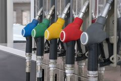 Blue, green, yellow, red and gray fuel pistols on fuel station close-up. Fuel pistols close up at the gas station close-up Royalty Free Stock Images