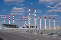 Fuel and power station pipes over road at blue sky background Stock Image
