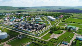 Fuel Processing Factory Territory against Scenery. Upper view fuel processing factory territory with industrial buildings surrounded by pipes against rural stock video footage