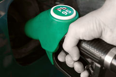 Fuel Pump Hand. Close-up of a man's hand using a petrol pump to fill his car up with fuel Royalty Free Stock Photography