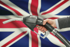 Fuel pump nozzle in hand with national flag on background - United Kingdom - UK - Great Britain. Fuel pump nozzle in hand with flag on background - United Royalty Free Stock Photos