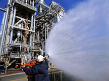 Fuel Refinery. A safety inspector tests a fire hose at a fuel refinery stock photo